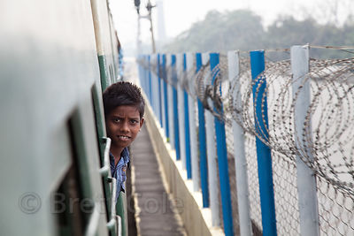 A boy leans out of a train near the Remount Railway Station, Kolkata, India.