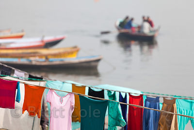 "Outdoor laundry (""Dhobi Ghat"") on the Ganges River, Varanasi, India. Workers wash the clothes by beating them on rocks, and then dry them on clothes lines and on the steps of Varanasi's famous ghats."