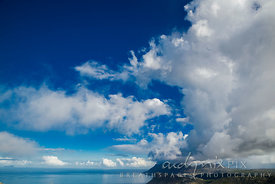 White cumulus clouds in a bright blue sky reflected in sea