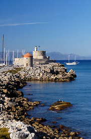 Windmills and Agios Nilolaos Fort besides Mandraki Harbour, Rhodes Town, Rhodes, Dodecanese Islands, Greece.