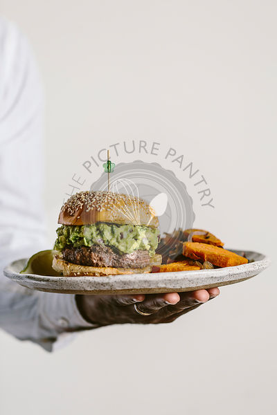 A man is photographed from the front view while holding a plate of guacamole burger and sweet potato fries.