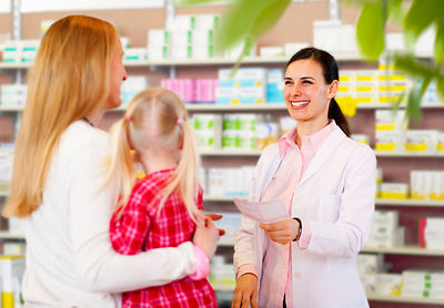 Pharmacist giving prescription to mother