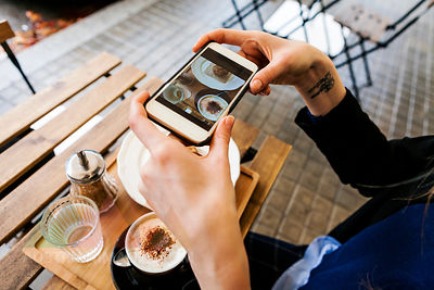 Woman in pavement cafe taking picture of her breakfast with cell phone