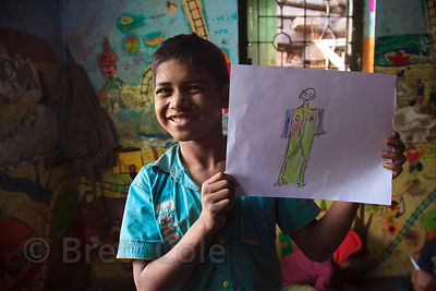 A boy hold up a drawing he made at the Child In Need Institute (CINI, cinindia.org) drop-in shelter at Sealdah Railway Station, Kolkata, India