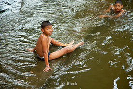 Two young boys cool down in the Chao Phray River in Bangkok, Thailand.