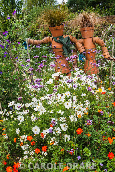Flowerpot figures surrounded by flowers, annuals and perennials, including Verbena bonariensis, white cosmos and tagetes.  RHS Garden Rosemoor, Great Torrington, Devon, UK