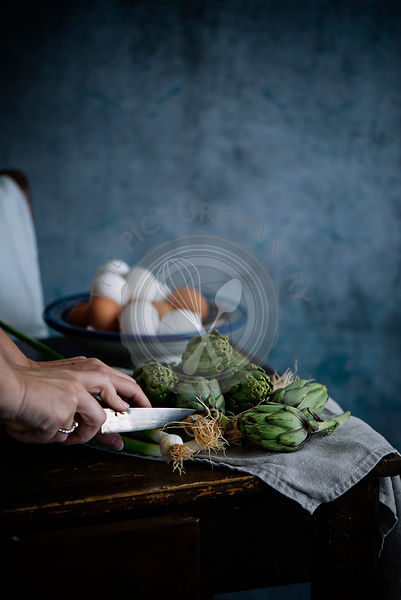 A woman chopping artichokes , with eggs in the background
