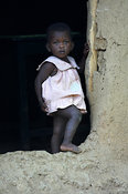Baby girl standing in entrance to mud hut Kenya Africa