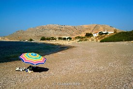 colouful sunshade on shingle beach, lardos, rhodes, dodecanese islands, Greece.