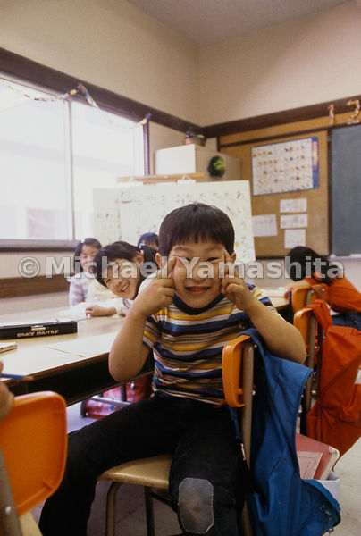 Class clown turns a gesture of ridicule into a good-natured acknowledgment of his heritage at a Buddhist school in Gardena, California.