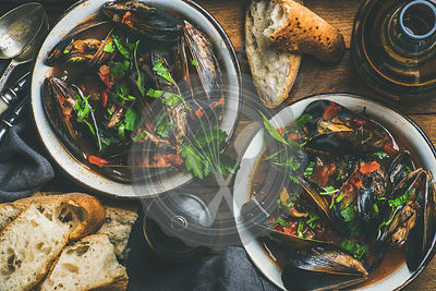 Flat-lay of Belgian boiled mussels in tomato sauce with fresh parsley in serving metal bowls, baguette bread slices and beer in bottle
