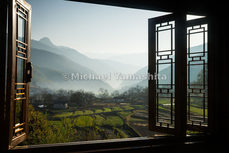 Windows at the Songtsam Tacheng lodge look out on terraced rice fields and misted peaks in Yunnan's northwest corner. The area around Tacheng, watered by the upper reaches of the mighty Yangtze River, is considered among the most fertile in Yunnan.