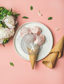 Flatlay of pastel pink strawberry and coconut ice cream scoops, sweet cones on white plate and white peonies over pastel pink background