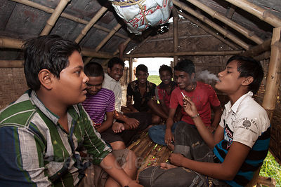 Teenagers from the town of Chingrihata smoke in a fishing hut in the East Kolkata Wetlands, Kolkata, India. Small hand-rolled cigarettes are very cheap and widely available in Kolkata.