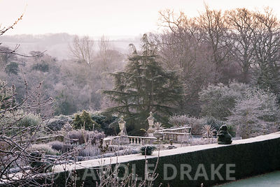 View from Temple Mount across the yew hedging bordering the croquet lawn to the formal terrace with balustrading and urns, trees and countryside of Dorset beyond. Kingston Maurward Gardens, Dorchester. Dorset, UK