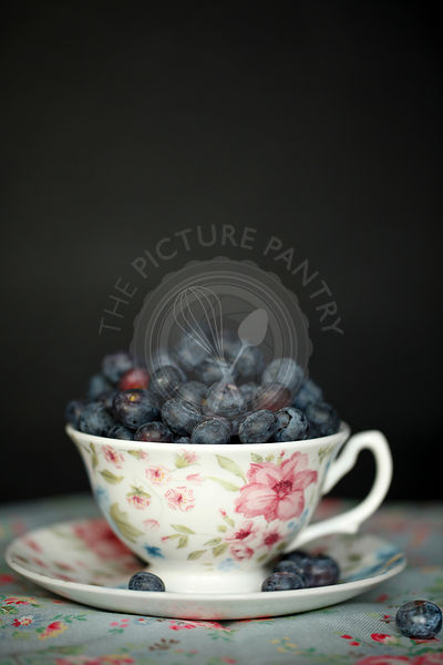 Vintage flower motif cup and saucer filled with blueberries, on floral tablecloth with a dark background.