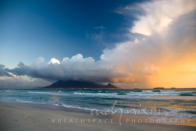 Cumulonimbus cloud over Table Mountain, setting sun illuminating underside of cloud and Lion's Head, four container ships in bay, waves breaking on beach in foreground