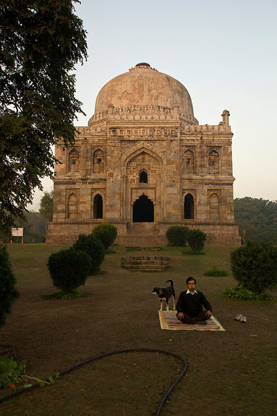 India - New Delhi - A man, joined by a stray dog, meditates at dawn outside the Bara Gumbad, Lodhi Gardens