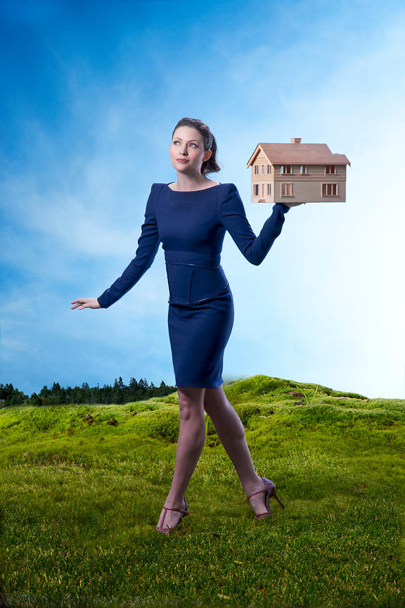 Woman walking and holding wooden house