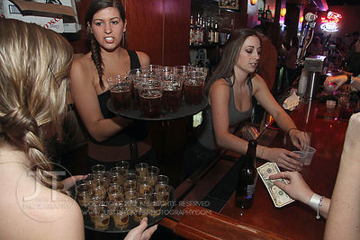 Bacardi promo girls and bartender Danielle Parker work at the Airliner Bar, 22 S Clinton Street in downtown Iowa City Saturday night. Copyright Justin Torner 2012 http://justintorner.photoshelter.com