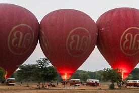 Hot air balloons firing up for tourist excursions over the ancient temples of Bagan, Myanmar.