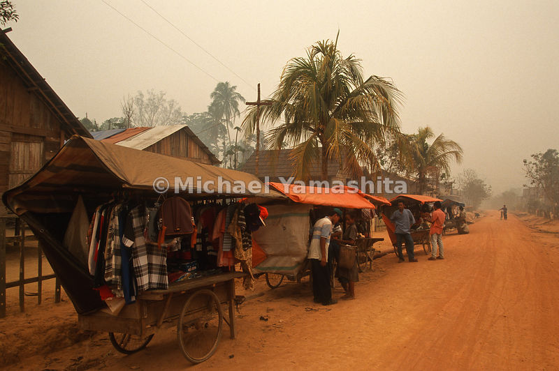 Vendors sell goods from their roadside market place.