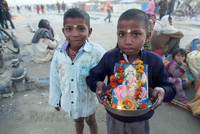 Two boys hold a religious idol at the 2013 Kumbh Mela, Allahabad, India.