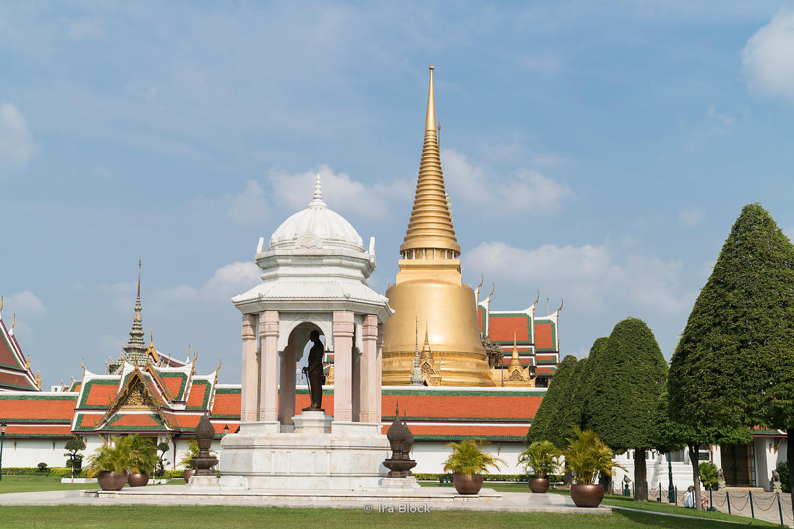A statue of the late King Rama Rama IX at the Grand palace in Bangkok with the Wat Phra Kaew temple in the background.