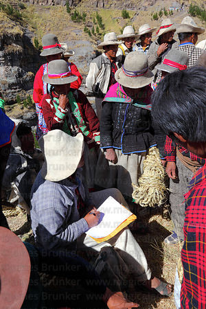 Community leader registering people who have provided new grass ropes to rebuild the bridge , Q'eswachaka , Canas province , Peru