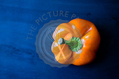 An orange pepper on a blue background