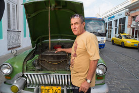 A man reparing a car on the street in Cienfuegos, Cuba.