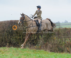 Marina Bealby jumping a hedge behind Waterloo Lodge