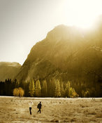 Tourist couple in mountain valley by sunny morning