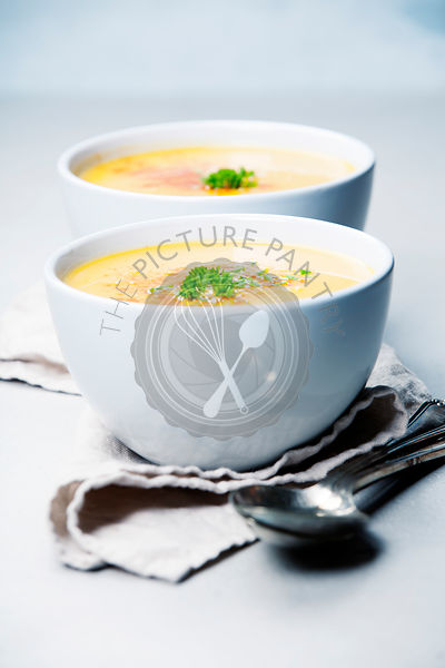 Pumpkin cream soup in bowl over grey concrete background, copy space, vertical composition