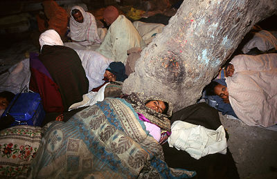 India - Allahabad - Pilgrims sleeping at the Kumbh Mela ready for their early morning dip in the Ganges