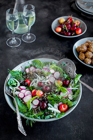 Cherry Wild Rice Salad with Hibiscus Vinaigrette served with white wine.  Photographed on a black/gray background.