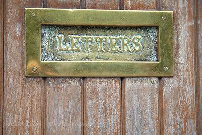 Brass letterbox in wooden door