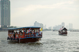 A commuter ferry crosses the Chao Phraya River in Bangkok, Thailand.
