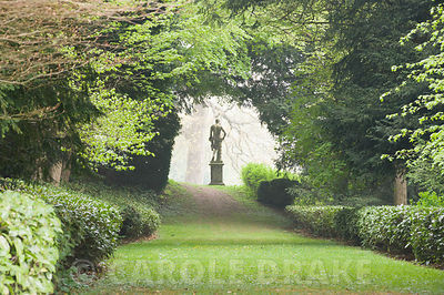 Statue of Apollo framed by trees at the end of the Long Walk, part of Charles Bridgeman's original garden scheme. Rousham House, Bicester, Oxon, UK