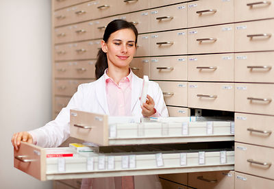 Pharmacist browsing medicine in drawers