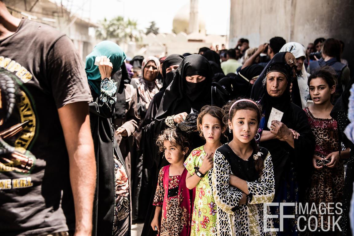 Tired, hot and fed up people queue for aid from a local NGO distribution, in West Mosul. June 2017