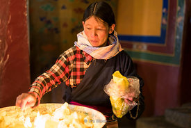 A woman and yak butter candles at Dreprung Monastery in Lhasa, Tibet.