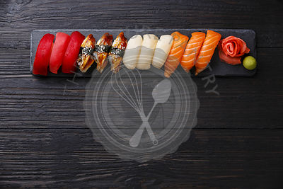 Nigiri Sushi set on stone slate on dark wooden background copy space