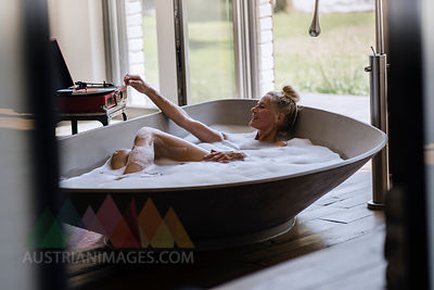 Mature woman taking bubble bath, listening music from analogue record player