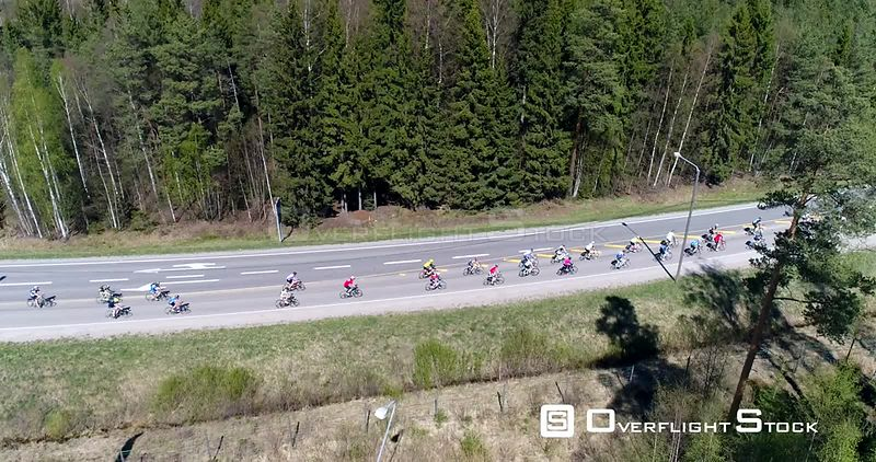 Bicycle race, Cinema 4k aerial rising view of a group of cyclists, racing on a cycle competition event, on a summer day, just outside Nuuksio national park, in Espoo, Finland