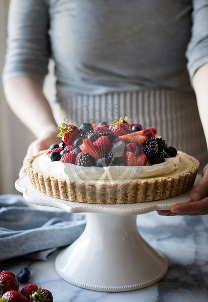 Woman with a No-Bake Lemon Berry Coconut Cream Tart with fresh berries (vegan, gluten-free, refined sugar-free) on a cake stand