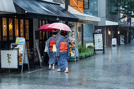 Maikos or Geishaa running into a cafe during heavy rain near Nishiki Market in Kyoto, Japan.