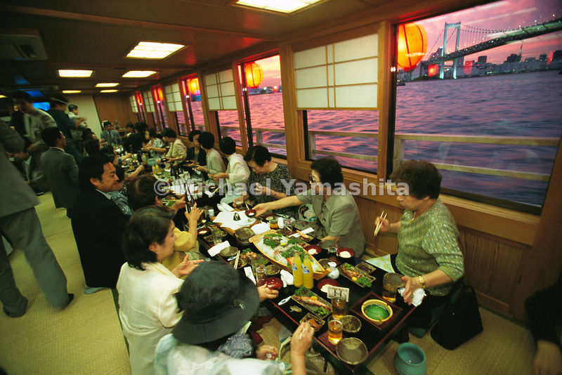 Aboard a yakatabune, a sight-seeing dinner boat, where diners indulge traditional tastes with ample sake. In the distance is the Rainbow Bridge - so named for its changing colored lights. Tokyo Bay, Japan.