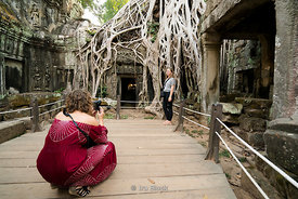 Tourists pose next to the Tetramelese tree growing over the Ta Prohm temple, originally called Rajavihara, at Angkor in Siem Reap, Cambodia.