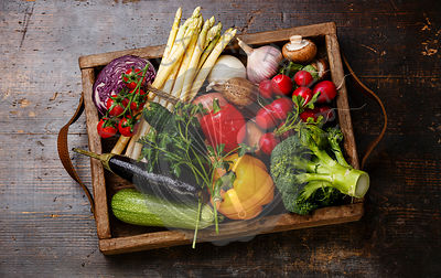 Fresh vegetables in wooden box on wooden background